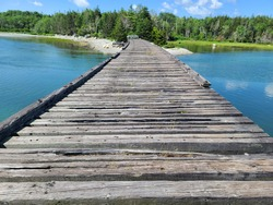 The top down view of the magnificent Old bridge at Summerville beach. The wooden planks are weathered and old. There's a barrier at the other side of the wooden roadway.