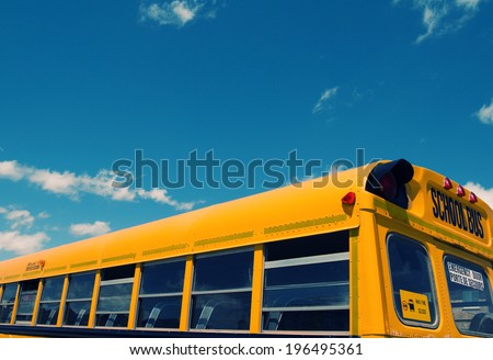 The top half of any empty school bus under a blue sky.