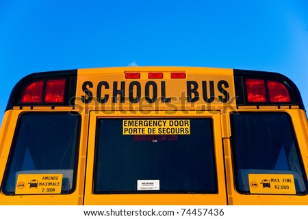 """The top half of the back of a yellow School Bus displaying the words """"School Bus"""" and """"emergency door""""."""