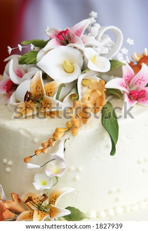The top of a beautiful wedding cake with a georgeous flower arrangement on top.