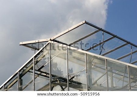 The top of a modern greenhouse, with its glass panels open to let in fresh air