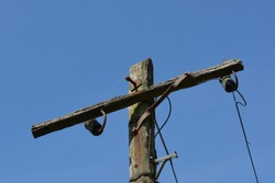 The top of a very old telegraph pole with weathered and rotted timber with rusted steel brackets all supporting a couple of cables against a blue sky.
