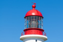 The top of a vintage lighthouse tower with a round red metal roof.  In the center of the lighthouse is a vintage lamp made of multiple pieces of glass. On top of the tower is a red metal wind arrow.