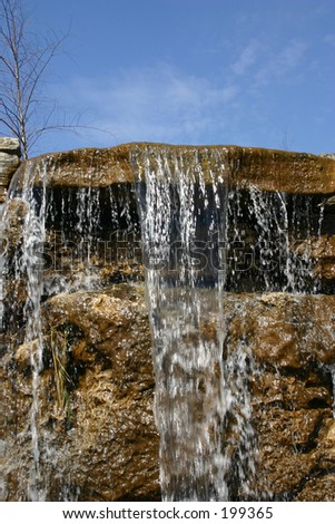 The top of a waterfall created in this garden by some good landscape contractors