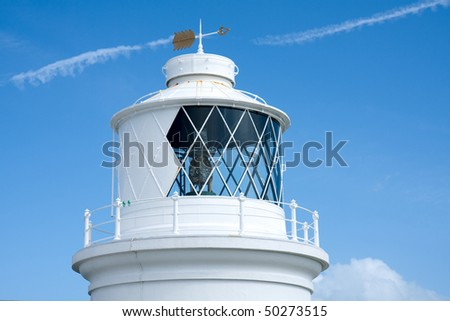 The top of a white lighthouse in Dorset, UK with an arrow shaped weather vane on the roof.