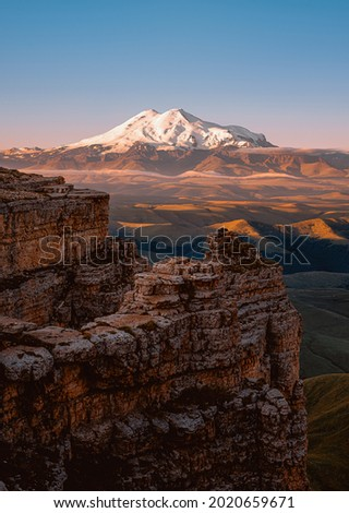 The top of Mount Elbrus. The Caucasus Mountains. View of Elbus from the Bermamyt plateau. A rock and a snow-covered sleeping volcano.