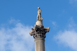 The top of Nelson's Column in Trafalgar Square, London, against a bright blue sky