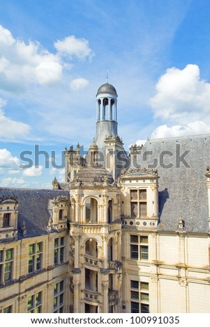 The top of the castle Chambord of a series of Chateau on the Loire River.Against the background of blue sky with clouds can be seen all the details of the roof,made on the project by Leonardo de Vinci - stock photo