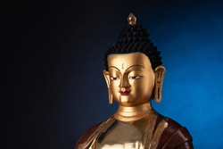 The top part of a gilded statue of Medicine Buddha, in traditional clothes with ushnisha on the head.  Isolated on black background with blue light spot.