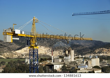 The top part of a tower crane raising above an industrial park located in rural surroundings.