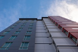 The top portion of a tall building with dark grey, light grey and red metal composite panels on the exterior wall of the skyscraper building. There's a blue sky with white clouds in the background.