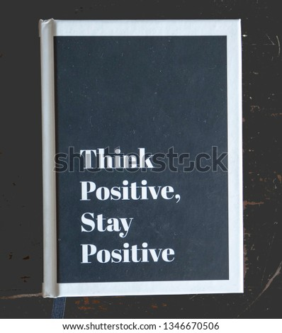 """The top view of a book, """"Think Positive, Stay Positive"""". The cover is black with the writing white and a white border. The background is dark. #1346670506"""