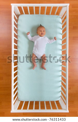 the top view of baby in cot - stock photo