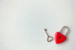 The top view shot of red heart padlock and key on white glitter background for valentines day with copy space
