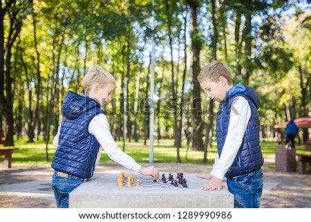 The topic is children learning, logical development, mind math, miscalculation moves advance. Big family two brothers Caucasian boys playing chess in the park in bright sunny weather in the autumn. #1289990986