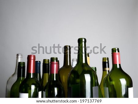 The tops of a lot of different colored bottles.