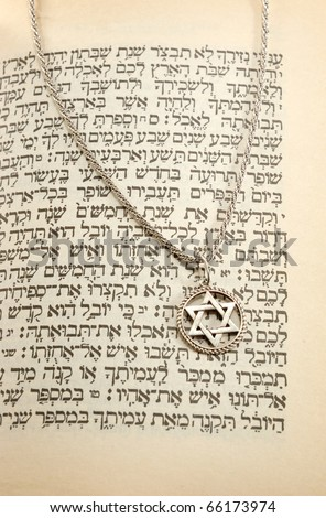 The Torah and silver chain with magen david still life