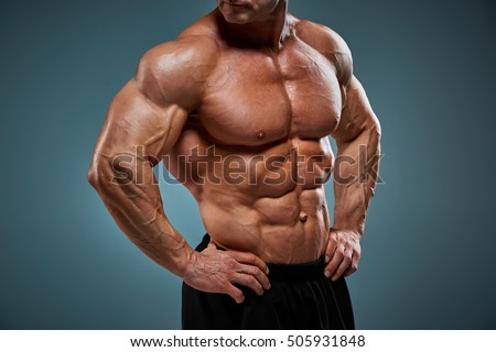 The torso of attractive male body builder on gray background. #505931848