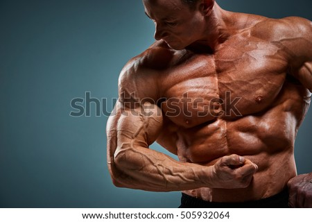 The torso of attractive male body builder on gray background. #505932064