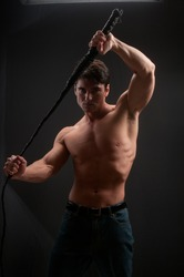 The tough guy holds a whip and prepares for battle.