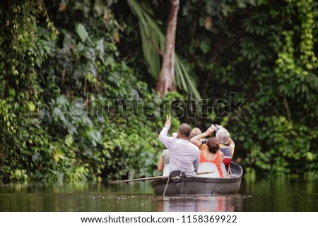The tour guide shows tourists in a canoe the beauty of the nature at a river in the Tortugero National Park, Costa Rica. #1158369922