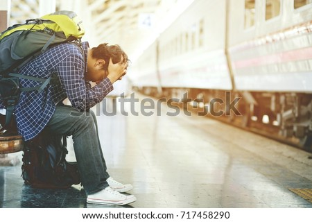 the tourist backpack man arrived late at the station. depressed and strain traveler sad sitting waiting at train station after mistakes a train makes wasting time in traveling.