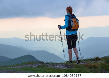 The tourist girl with back sack and tracking sticks is staying on the lawn. Beautiful cloudy sky. Sun rays fall down on the mountains. Summer scene. Eco touristic laisure time. #1084050137