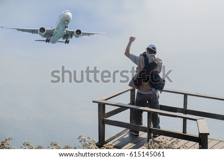 The tourist taking photo with the airplane on blue light sky background