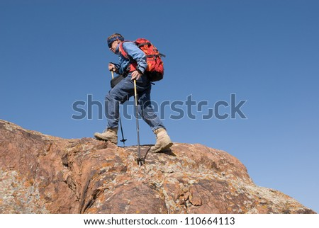 The tourist with a backpack runs on a rocky crest