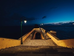 the tourists standing on the pier and looking at the sea in the evening