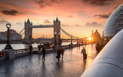 The Tower Bridge in London during sunrise and people rushing to their work