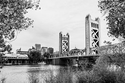 The Tower Bridge, vertical lift bridge, and city skyline in Sacramento, California, USA beyound tree branches during the autumn season