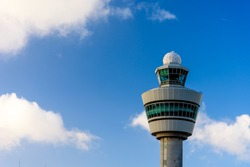 The tower in airport in Amsterdam. The tower against blue cloudy sky. Control tower in airport. Aviation observation post in airport in Netherlands.
