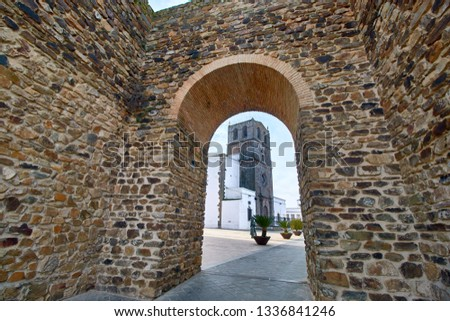 The tower of Santa Maria Magdalena seen through the door of the Arab wall in Olivenza Badajoz Spain