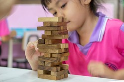The tower stack from wooden blocks toy on table in classroom. Infant developmental accessories.