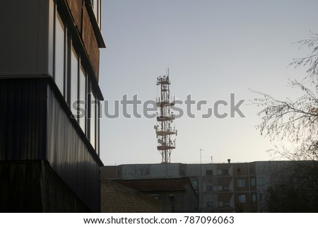 The tower with cellular, radio, television antennas is installed on the roof of the house. Industrial background #787096063