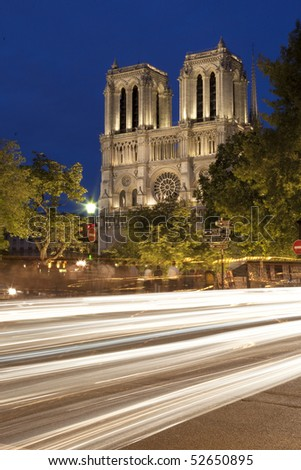 The towers of the Notre Dame Cathedral in Paris, France at night.  Lights from cars can be seen in the foreground. Vertical shot.