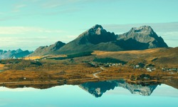 the town Borg is reflected in the mirror of the lake. Autumn nature landscape of Norway on Lofoten islands.