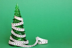 The toy Christmas tree is wrapped with a centimeter tape. Consequences of new year's holidays for the figure. Diet after the new year holidays concept.