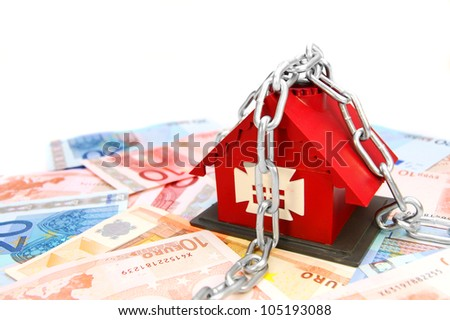 The toy house and chain with money. On a white background.