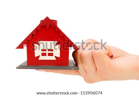 The toy house in hand. On a white background.