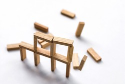 The toy wooden block structure building broken and dropped down on white background