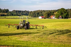 The tractor and hay tedder prepare hay harvest for cultivation. Agriculture and agronomy concept. Selective focus