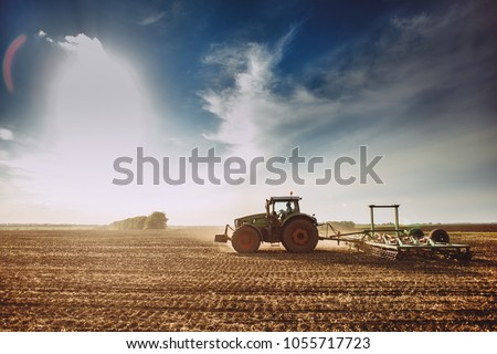 the tractor plows the field against a dramatic sunset