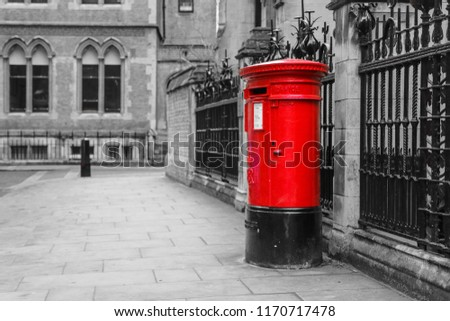 The traditional British red post box in London standing on the street. Isolated in a black and white picture.