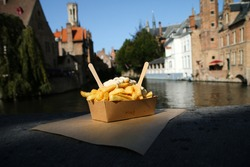 The traditional street food snack, the Belgian Fries with pepper sauce pictured on the wall over the channel in Bruges in Belgium.