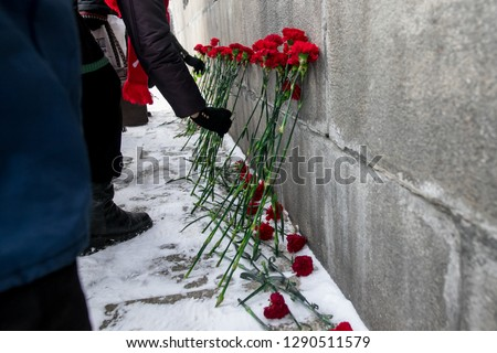 The tragedy of the innocent victims. The memory of the victims. A symbol of mourning. The loss from a terrorist attack. Red flowers.