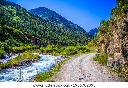 The trail next to the mountain river. Mountain river canyon landscape. River in mountains. Mountain river view
