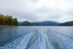 The trail of the boat (Wake) on the lake in the middle of the mountains and fog in the autumn. Boat trip on the lake in autumn in Alaska