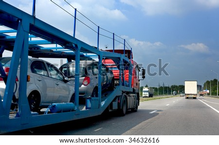 The trailer transports cars on highway #34632616